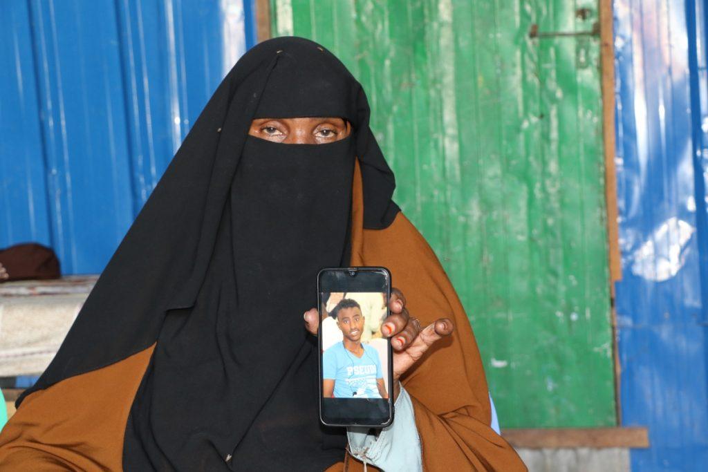 Sahra Ismail Ali, 53-year-old presents a photo of her murdered son, Abdirizak Qasim Iman, a Somali camera-journalist killed by a police officer in Mogadishu. (PHOTO by Hinda Dahir on Friday July 24, 2020).